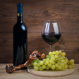 Bottle and glass of red wine, grapes and corkscrew made of grapevine Royalty Free Stock Image