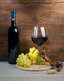 Bottle and glass of red wine, grapes and corkscrew made of vine. Bottle and glass of red wine, grapes and corkscrew made of grapevine on a wooden background Stock Photo