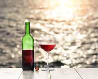 Bottle and glass of red wine on the linen table against the sea or ocean Stock Photography