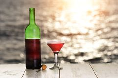 Bottle and glass of red wine on the linen table against the sea or ocean on sunset royalty free stock photo