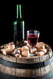 Bottle and glass of red wine on old barrel with stopper Royalty Free Stock Photos