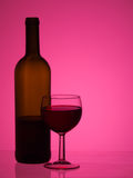 Bottle and glass of red wine over bright pink background. With copyspace. Pink backlighting to achieve striking effect. Ideal party poster etc Royalty Free Stock Images