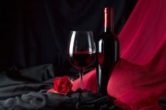 Bottle and glass of red wine . Bottle and glass of red wine with red silk and red rose on black background. Copy space stock photos