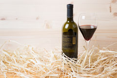 Bottle and glass of red wine in straw Stock Photo