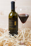 Bottle and glass of red wine in straw Royalty Free Stock Photography