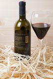 Bottle and glass of red wine in straw Royalty Free Stock Photo