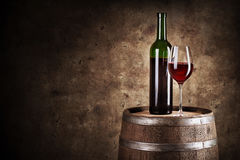 Bottle and glass of red wine on wooden barrel. Shot with dark background Royalty Free Stock Image