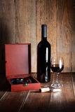 Bottle and glass of red wine on wooden table. Stock Photography