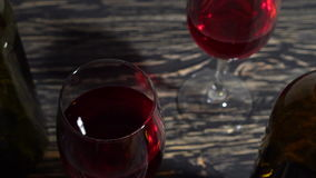 Bottle and glass of red wine on a wooden table. Bottle and glass of red wine on a wooden background stock video footage