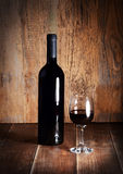 Bottle and glass of red wine on wooden table. Stock Photos