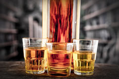 Bottle and glass shots with yellow liqour Royalty Free Stock Images