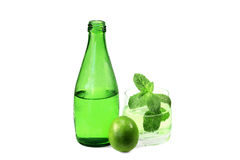 Bottle and glass of sparkling mineral water with lime and meliss Royalty Free Stock Images