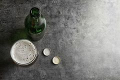 Bottle and glass with tasty cold beer. On grunge background, top view stock photo