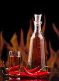 Bottle,  glass  vodka, red hot chili pepper on  background  flames. Stock Photos
