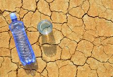 Bottle and glass of water on dry cracked soil. Royalty Free Stock Images