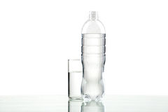 Bottle and glass with water on white background. Bottle and glass with water on white background close up Royalty Free Stock Photos
