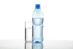 Bottle and glass with water on white background. Bottle and glass with water on white background close up Royalty Free Stock Photography