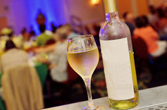 Bottle and glass of white wine. On a table in a restaurant Royalty Free Stock Image