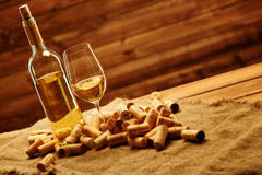 Bottle and glass of white wine on a wooden table among corks Royalty Free Stock Image
