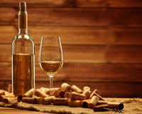 Bottle and glass of white wine on a wooden table among corks Stock Photography