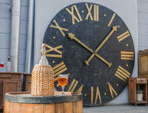 Bottle and glass of wine on a barrel on the background of the clock. Bottle and glass of wine on a barrel Stock Photos