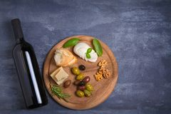 Bottle and glass of wine with cheese, olives, bread, nuts and rosemary on dark background. Wine and food concept, banner. Overhead, horizontal Stock Image