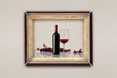 Bottle and glass of wine in the frame on the wall Royalty Free Stock Photos
