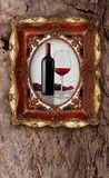 Bottle and glass wine in old picture frame on wood background Royalty Free Stock Photo