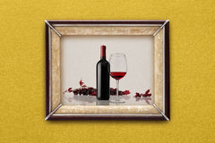 Bottle and glass of wine in the picture frame on the wall Royalty Free Stock Image