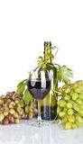 Bottle, glass of wine and ripe grapes  on white Stock Image