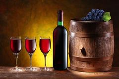 Bottle and a glass of wine with a wooden barrel. On dark yellow background with a gradient royalty free stock image