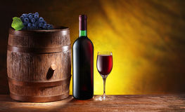 Bottle and a glass of wine with a wooden barrel Stock Photography
