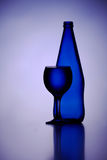 A bottle of glass and wineglass in blue.  Royalty Free Stock Photography