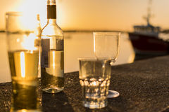 Bottle and glasses of alcohol by the sea Royalty Free Stock Photography