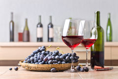 Bottle and glasses of red wine on the kitchen table. Bunch of blue grapes and corkscrew on a kitchen ceramic table royalty free stock photography