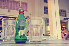 Bottle and Glasses on the Table of an Open Air Cafe in the Evening; Retro Lifestyle Concept Stock Images