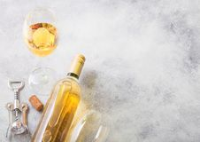 Bottle and glasses of white wine with cork and crkscrew opener on stone kitchen table background. Top view. Space for text royalty free stock photos