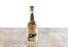 Bottle and grains. Isolate  on and wood white background Royalty Free Stock Photos
