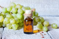Bottle with grape seed essential oil on a wooden table. stock photo