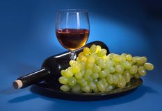 A bottle of grape wine and white grapes on a blue background stock photography