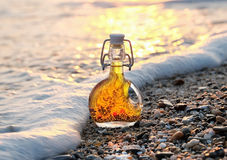 The bottle of Greek olive oil on the sea stony beach in the sea foamy wave Stock Photo