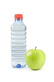 Bottle and green apple. Bottle of mineral water with green apple Stock Photo