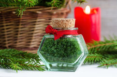 Bottle of green bath salt and fir branches. Christmas health care gift. Spa concept. Royalty Free Stock Image