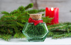 Bottle of green bath salt and fir branches. Christmas health care gift. Spa concept. Royalty Free Stock Photo