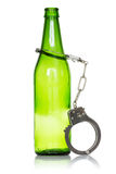 Bottle and handcuffs Stock Images
