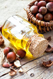 Bottle of  healthy nut oil and basket with hazelnuts on table Royalty Free Stock Image