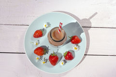 Bottle of healthy strawberry smoothie on the blue plate Royalty Free Stock Photos