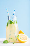 Bottle of homemade lemonade with mint, ice, lemons, paper straws and pastel blue background Stock Photos