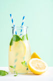 Bottle of homemade lemonade with mint, ice, lemons, paper straws and pastel blue background Royalty Free Stock Photo