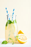 Bottle of homemade lemonade with mint, ice, lemons, paper straws and pastel blue background Stock Photo